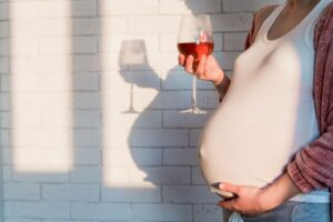Yahoo - Pregnant woman holding glass of wine